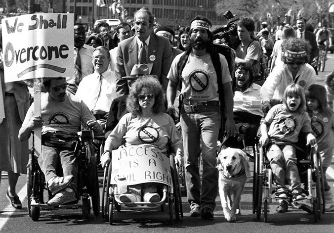 "A black and white photo of a group of people marching. Some people are using wheelchairs and some are walking. They are holding signs that say ""We shall overcome"" and ""Access is a civil right."""