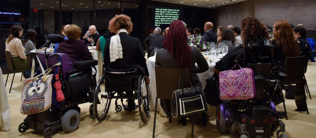 Several women watch a presentation on a screen in front of them. They are seated in chairs and wheelchairs, and are surrounded by other conference attendees.