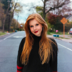 Headshot of Leslie Templeton, a white female with red hair and silver hoop earrings, smiling. Wearing a Black turtle neck sweater with red stripes on the lower part of the sleeves. Standing in the middle of the road with trees in the background.