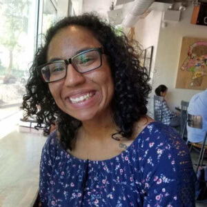 Headshot of Valerie Novack, a Biracial person with curly black hair is smiling for the camera. She has black-rimmed glasses and is wearing a blue, flowered romper. She is seated in a coffee shop, backs of patrons visible behind her.
