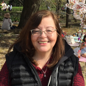 Headshot of Dr. Yolanda Muñoz, a white, middle-aged woman with long brown hair. She wears glasses and is smiling to the camera. She's outdoors in a sunny day.